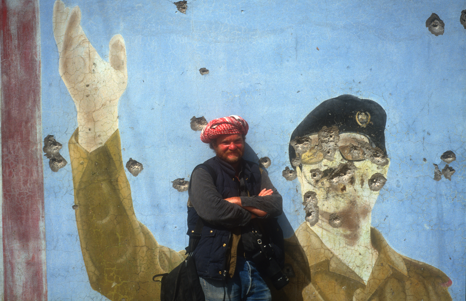 1991: Northern Iraq, in front of bullet riddled portrait of Saddam Hussein