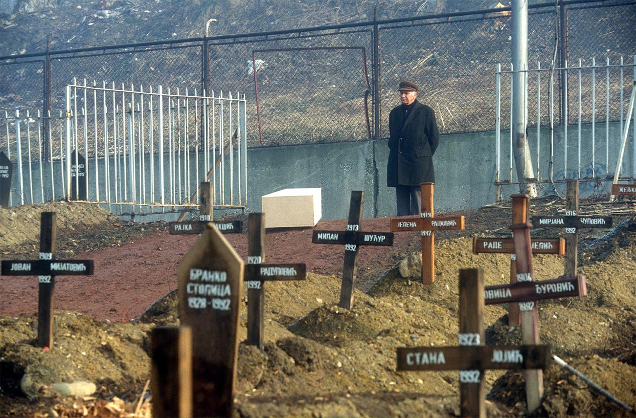 1993. Homme avec cercueil de sa femme attend le fossoyeur. Cimetière du Lion à Sarajevo.